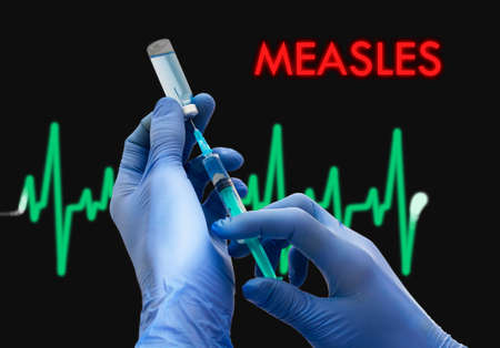 measles: Treatment of measles. Syringe is filled with injection. Syringe and vaccine. Medical concept. Stock Photo