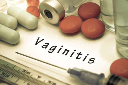 sexual intercourse: Vaginitis - diagnosis written on a white piece of paper. Syringe and vaccine with drugs