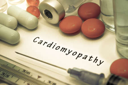 injection valve: Cardiomyopathy - diagnosis written on a white piece of paper. Syringe and vaccine with drugs.