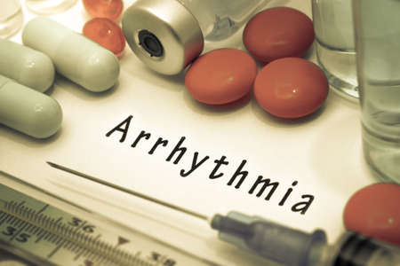 fibrillation: Arrhythmia - diagnosis written on a white piece of paper. Syringe and vaccine with drugs. Stock Photo
