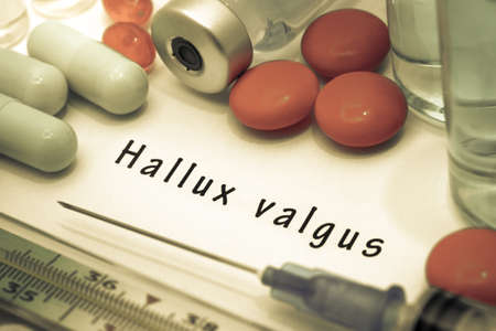 bunion: Hallux valgus - diagnosis written on a white piece of paper. Syringe and vaccine with drugs. Stock Photo