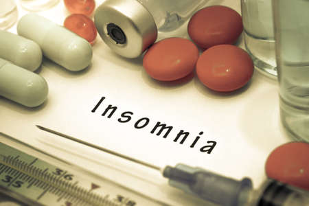 insomniac: Insomnia - diagnosis written on a white piece of paper. Syringe and vaccine with drugs. Stock Photo