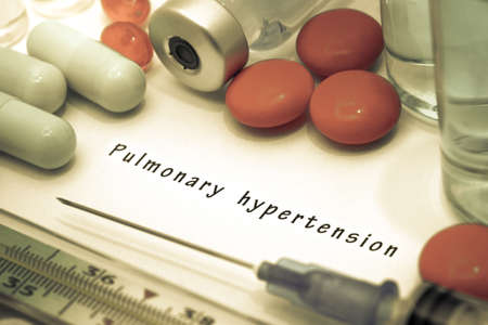embolism: Pulmonary hypertension - diagnosis written on a white piece of paper. Syringe and vaccine with drugs. Stock Photo