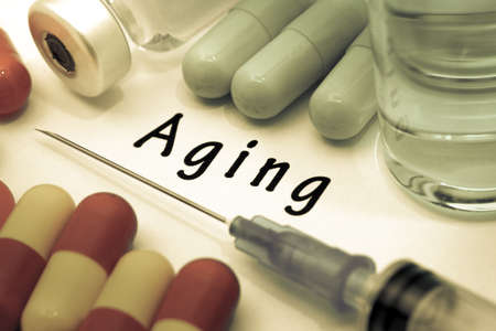 degenerative: Aging - diagnosis written on a white piece of paper. Syringe and vaccine with drugs Stock Photo