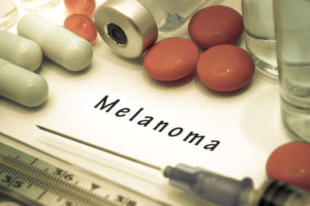 lesions: Melanoma - diagnosis written on a white piece of paper. Syringe and vaccine with drugs.