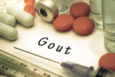 gout: Gout - diagnosis written on a white piece of paper. Syringe and vaccine with drugs.