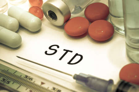 std: STD - diagnosis written on a white piece of paper. Syringe and vaccine with drugs