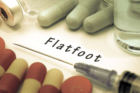 flatfoot: Flatfoot - diagnosis written on a white piece of paper. Syringe and vaccine with drugs.