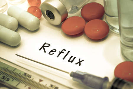sphincter: Reflux- diagnosis written on a white piece of paper. Syringe and vaccine with drugs.