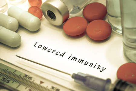 inmunidad: Lowered immunity - diagnosis written on a white piece of paper. Syringe and vaccine with drugs.