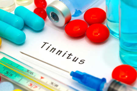decibel: Tinnitus - diagnosis written on a white piece of paper. Syringe and vaccine with drugs.