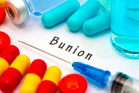 bunion: Bunion - diagnosis written on a white piece of paper. Syringe and vaccine with drugs.
