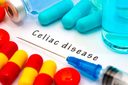 coeliac: Celiac disease - diagnosis written on a white piece of paper. Syringe and vaccine with drugs.