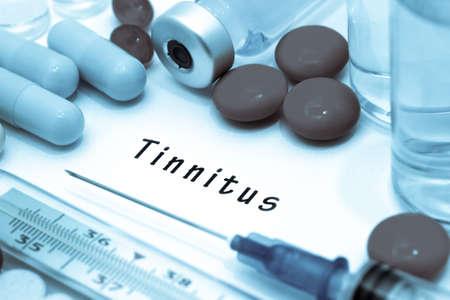 dolor de oido: Tinnitus - diagnóstico por escrito en un pedazo de papel blanco. Jeringa y la vacuna con las drogas.