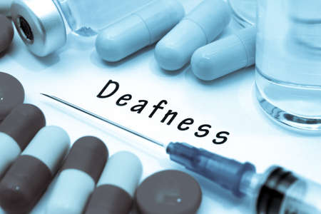 deafness: Deafness - diagnosis written on a white piece of paper. Syringe and vaccine with drugs.