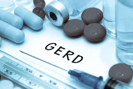 sphincter: GERD - diagnosis written on a white piece of paper. Syringe and vaccine with drugs