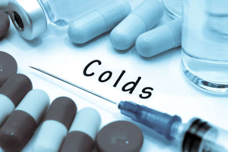 colds: Colds - diagnosis written on a white piece of paper. Syringe and vaccine with drugs.