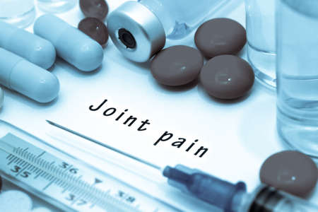 anklebone: Joint pain - diagnosis written on a white piece of paper. Syringe and vaccine with drugs.