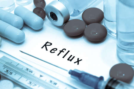 Reflux- diagnosis written on a white piece of paper. Syringe and vaccine with drugs.