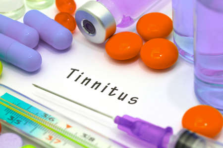 dolor de oido: Tinnitus - diagnosis written on a white piece of paper. Syringe and vaccine with drugs.