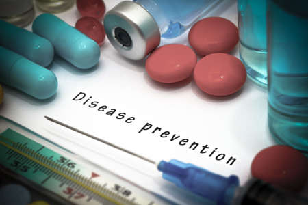 disease prevention: Disease prevention - diagnosis written on a white piece of paper. Syringe and vaccine with drugs. Stock Photo