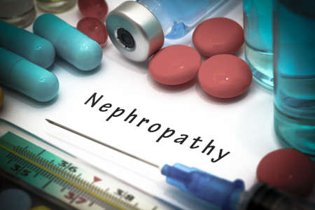 Nephropathy - diagnosis written on a white piece of paper. Syringe and vaccine with drugs. Stock Photo
