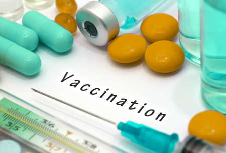 inoculate: Vaccination - diagnosis written on a white piece of paper. Syringe and vaccine with drugs. Stock Photo