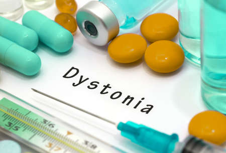 Dystonia - diagnosis written on a white piece of paper. Syringe and vaccine with drugs. Standard-Bild