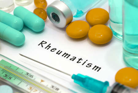 rheumatism: Rheumatism - diagnosis written on a white piece of paper. Syringe and vaccine with drugs. Stock Photo