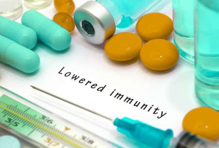 inmunidad: baja inmunidad - diagn�stico por escrito en un pedazo de papel blanco. Jeringa y la vacuna con las drogas.