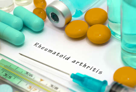 stiffness: Rheumatoid arthritis - diagnosis written on a white piece of paper. Syringe and vaccine with drugs. Stock Photo