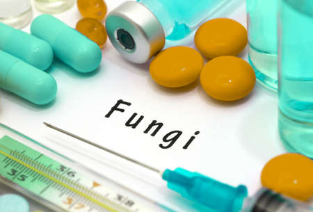 malaise: Fungi - diagnosis written on a white piece of paper. Syringe and vaccine with drugs. Stock Photo