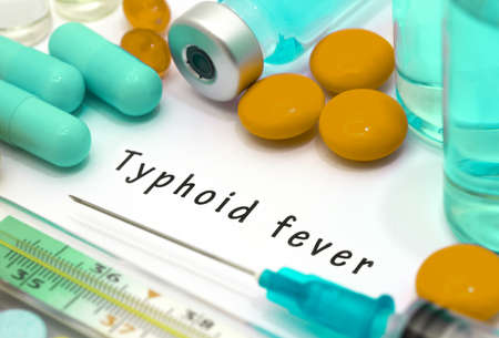 Typhoid fever - diagnosis written on a white piece of paper. Syringe and vaccine with drugs.