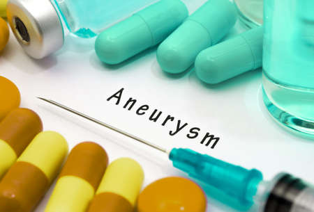 Aneurysm - diagnosis written on a white piece of paper. Syringe and vaccine with drugs.