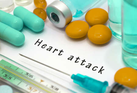 Heart attack - diagnosis written on a white piece of paper. Syringe and vaccine with drugs. Stock Photo