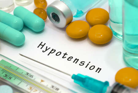 hypotension: Hypotension - diagnosis written on a white piece of paper. Syringe and vaccine with drugs. Stock Photo