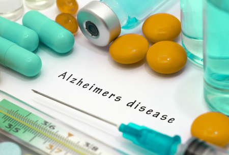 Alzheimers disease - diagnosis written on a white piece of paper. Syringe and vaccine with drugs. Stock Photo