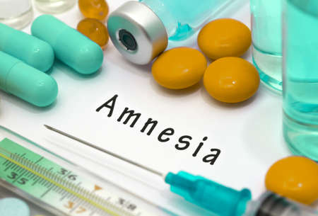 amnesia: Amnesia - diagnosis written on a white piece of paper. Syringe and vaccine with drugs. Stock Photo