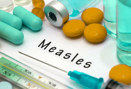 det: Measles - diagnosis written on a white piece of paper. Syringe and vaccine with drugs. Stock Photo