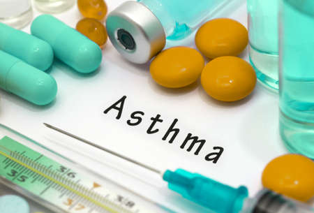 Asthma - diagnosis written on a white piece of paper. Syringe and vaccine with drugs.