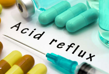 acid reflux: Acid reflux - diagnosis written on a white piece of paper. Syringe and vaccine with drugs.