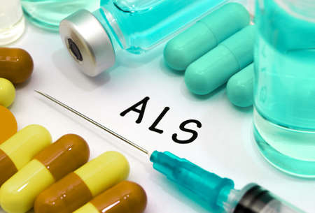 ALS (amyotrophic lateral sclerosis) - diagnosis written on a white piece of paper. Syringe and vaccine with drugs. Stock Photo