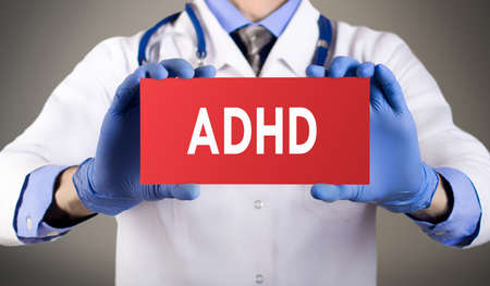 inattention: Doctors hands in blue gloves shows the word ADHD (attention deficit hyperactivity disorder). Medical concept.