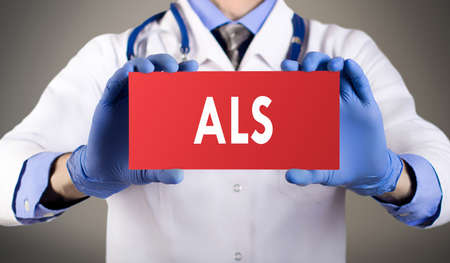 Doctor's hands in blue gloves shows the word ALS (amyotrophic lateral sclerosis). Medical concept.