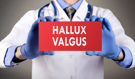 bunion: Doctors hands in blue gloves shows the word hallux valgus. Medical concept.