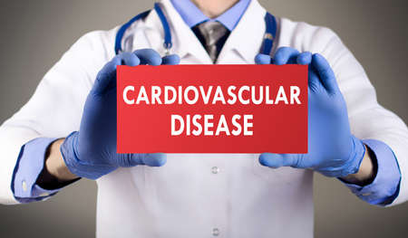 inflamation: Doctors hands in blue gloves shows the word cardiovascular disease. Medical concept.