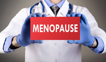progesterone: Doctors hands in blue gloves shows the word menopause. Medical concept.