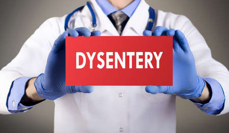 protista: Doctors hands in blue gloves shows the word dysentery. Medical concept.