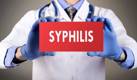 syphilis: Doctors hands in blue gloves shows the word syphilis. Medical concept.