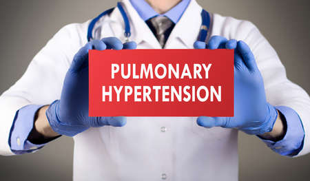 embolism: Doctors hands in blue gloves shows the word pulmonary hypertension. Medical concept.